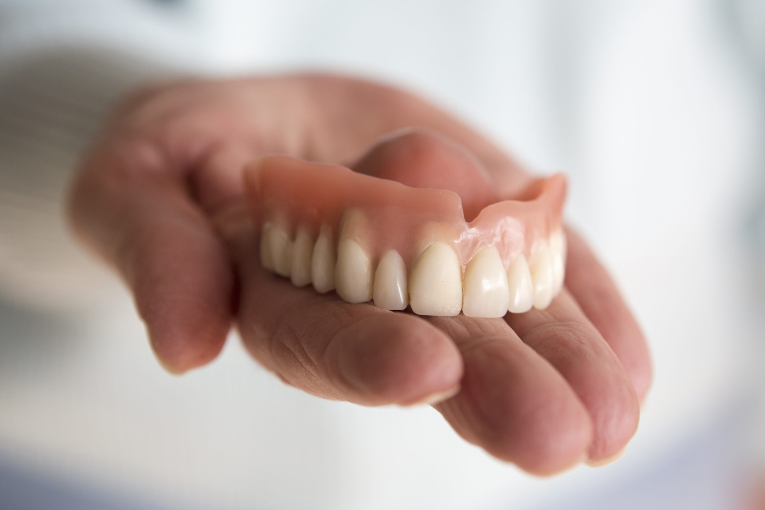 Closeup of dentures in a woman's hand